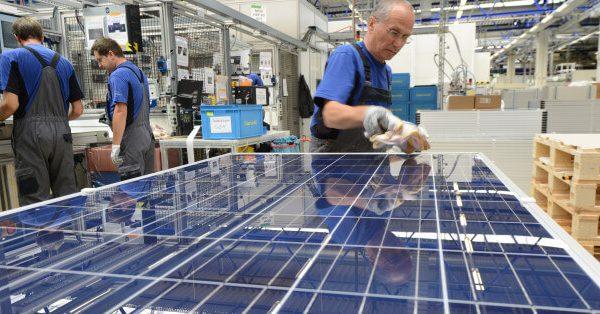 operai che producono pannelli fotovoltaici